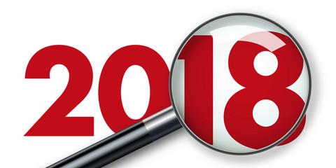 Concept de présentation d'un bilan d'entreprise 2018 vu au travers d'une loupe symbole de l'analyse