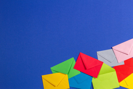Colorful envelopes on blue background, top view