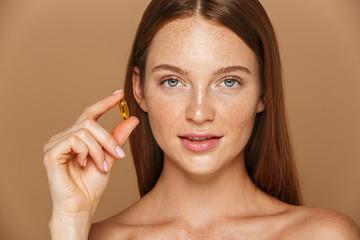 Fototapeta Beauty image of european shirtless woman 20s holding vitamin pill, isolated over beige background obraz