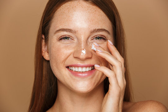 Beauty image of pretty shirtless woman smiling and applying face cream, isolated over beige background