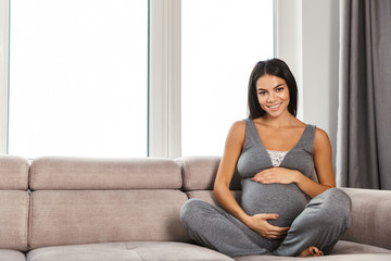 Healthy pregnant woman indoors at home sitting posing.