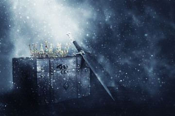 mysterious and magical image of old crown, wooden chest and sword over gothic black background. Medieval period concept.