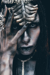 Portrait of woman in image of extraterrestrial alien with horns on her head and demonic eyes.