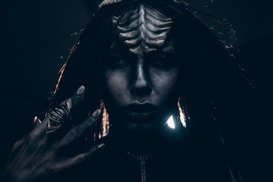 Portrait of young woman in image of extraterrestrial alien with finger ring on her hand and demonic eyes.