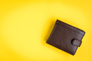 Brown men's wallet on yellow background.