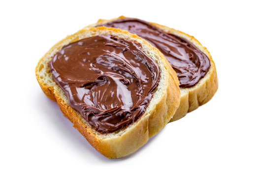 Isolated pieces of loaf with spread chocolate paste on a white background. Sweet, nut paste with fresh bread for breakfast.
