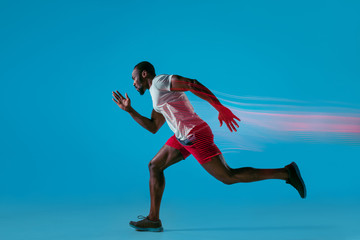 Full length portrait of active young muscular running man,