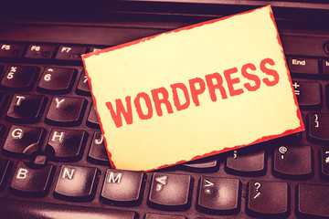 Writing note showing Wordpress. Business photo showcasing free source publishing software that can installed web server Blank Bordered Notepad Reminding Inserted Between Keys of Laptop