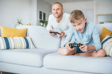 Father watching his son playing TV video game using the gamepad in the living room. Modern game devices concept.
