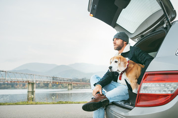 Breaded man in warm casual autumn outfit siting with beagle in car trunk. Traveling with pets concept.