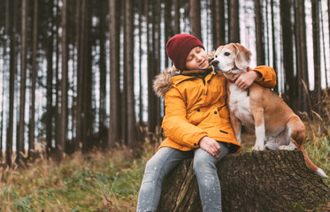Fototapete - Two huging best friends portrait - boy and his beagle dog sit on the tree stump in the autumn pine forest