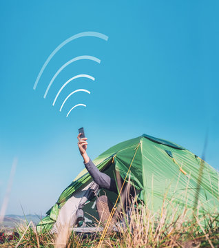 Traveler sits in touristic camping tent and tries to catch cellular network. Cell web coverage and roaming concept image.