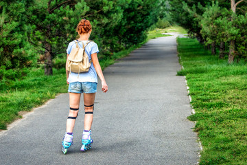 Sporting girl rollerscating in park fir alley on summer day.