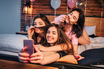 Three playful young women taking selfie on bed in room. Two models play with hair of third girl. They look on camera, pose and smile. Girls look happy.