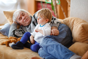 cute little toddler boy and grandfather watching together tv show. Baby grandson and happy retired senior man sitting together at home with cartoons on television. Calm family time.