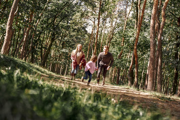 Happy parents with their daughter hold hands and run at forest path