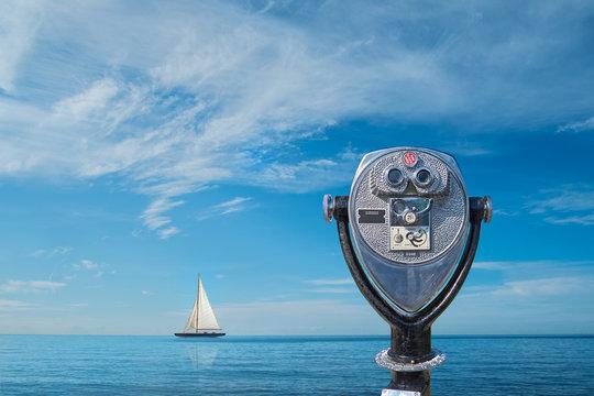 Binocular viewer overlooking sea with yacht on horizon