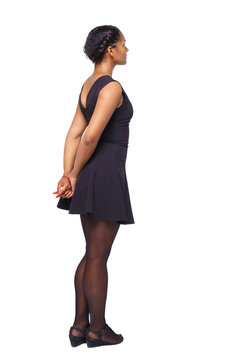Side view of black woman in a brown dress.