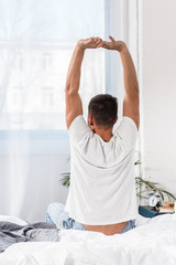 rear view of man stretching in morning in bedroom