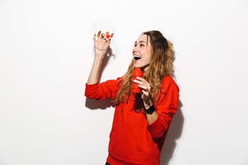 Image of pretty woman 20s wearing red sweatshirt blowing soap bubbles, isolated over white background