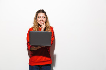 Image of amusing woman 20s wearing red sweatshirt holding laptop, isolated over white background