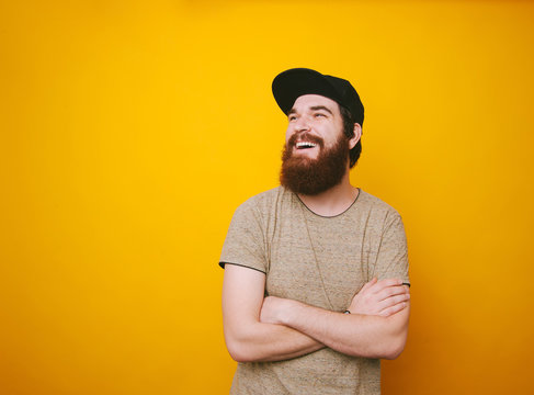 Portrait of cheerful bearded man smiling and looking away over yellow background