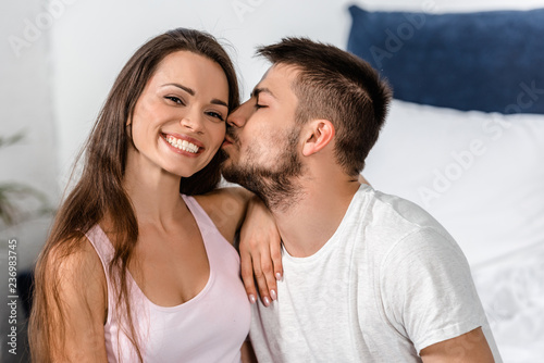4d8c7b345a boyfriend in pajamas hugging and kissing smiling girlfriend on bed in  bedroom