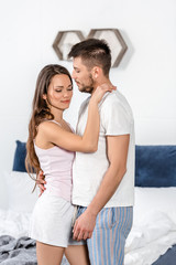 boyfriend and girlfriend in pajamas hugging in bedroom