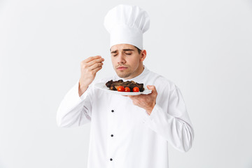 Cheerful chef cook wearing uniform peppers