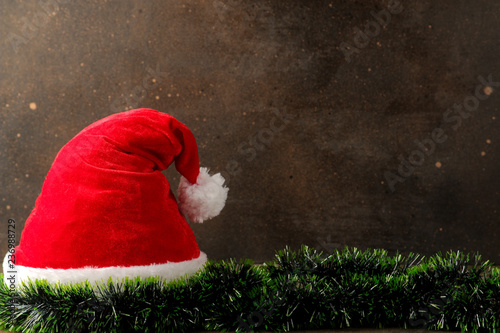 a82ae7370a016 Red Santa Claus hat and garland on a dark brown background. with space for  text