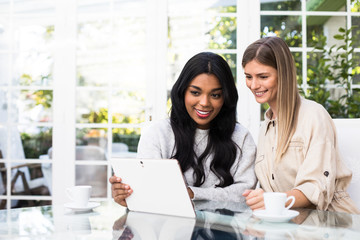 Two beautiful female friends smiling and browsing modern tablet while sitting at glass table in stylish room together