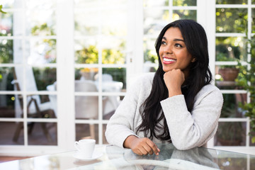 Beautiful African American woman smiling and looking away while sitting at glass table with cup of hot beverage in stylish room