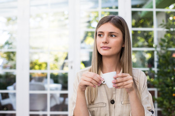 Lovely young lady looking away while enjoying hot beverage in stylish room