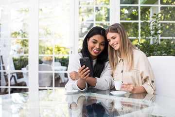 Pretty young female smiling and demonstrating modern smartphone to cheerful friend while sitting at glass table together