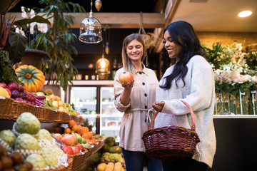 Two lovely female friends smiling and looking at fresh fruit while standing in grocery store