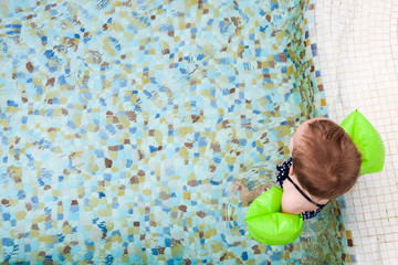 Baby girl with inflatable armbands. Child learning to swim in the pool. Copy space