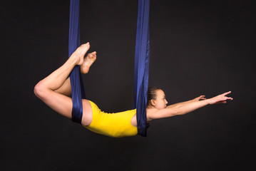 Young, smiling girl doing exercises on a loop of aerial silk .