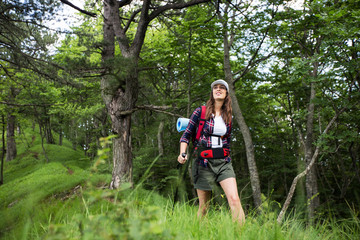 Young female hiker with backpack in a forest