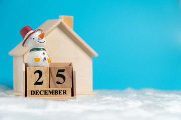 Snowman sitting on wooden block calendar set on 25 december on white wool in front of Wooden house. Copy space for text or content. Concept of Christmas day.