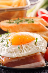 Fried egg with bacon with fried pieces of bread, greens and tomatoes. Close-up.