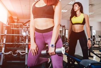 Beautiful athletic young women making exercise at the gym. Young woman with muscular body.