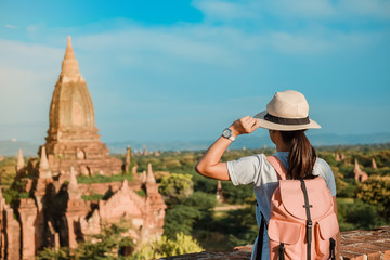 Fototapete - Young woman traveling backpacker with hat, Asian traveler standing on Pagoda and looking Beautiful ancient temples, landmark and popular for tourist attractions in Bagan, Myanmar. Asia Travel concept