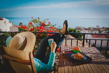 young woman having breakfast relax on scenic balcony terrace at sea