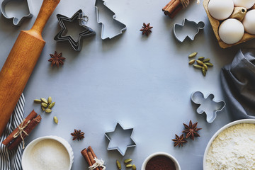 Cooking Christmas cookies. Ingredients for gingerbread dough: flour, eggs, sugar, cocoa, cinnamon sticks, anise stars and cookie cutters on gray wooden background. Flat lay. Copy space. Toned