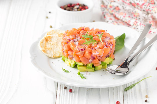 Salmon tartare with red onion, avocado, arugula, bread toast. Beautiful snack, dietary food, appetizer for Christmas holiday. On white wooden background