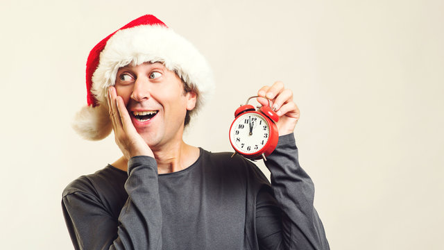 Surprised man in Santa helper hat with clock. Last minute christmas shopping. Time is coming. New Year and Christmas. Christmas sales, discounts, and holidays. Copy space.