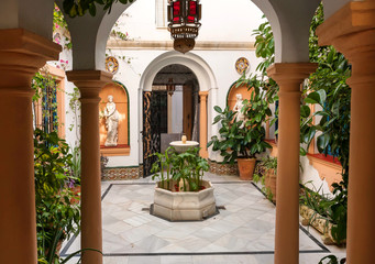 Traditional courtyard with columns, vintage sculptures and decor of Andalusia. Historical houses in Cordoba, Spain