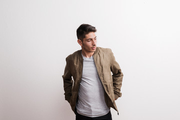 A confident young hispanic man in a studio, hands in pockets.
