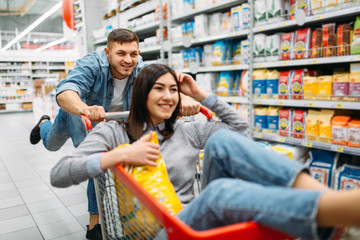Husband carries his wife in the cart, supermarket