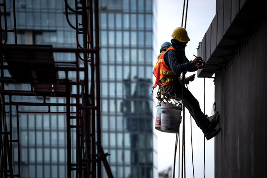 Construction worker wearing safety harness and safety line working at high place